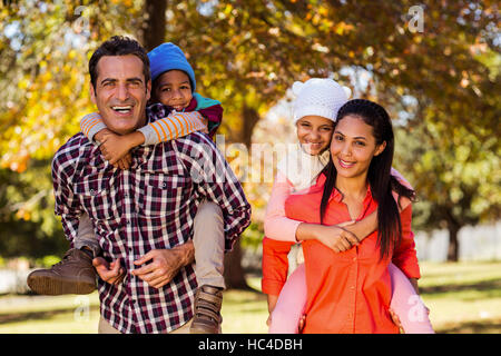 Parents piggybacking children at park - Stock Photo