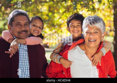 Happy grandparents piggybacking grandchildren at park
