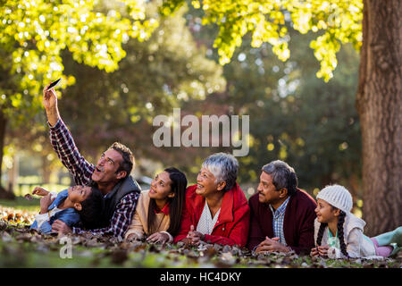 Man with family taking selfie at park - Stock Photo