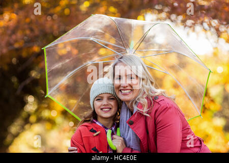 Mother and daughter embracing while holding umbrella - Stock Photo