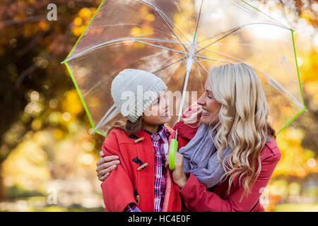 Happy mother and daughter holding umbrella at park - Stock Photo