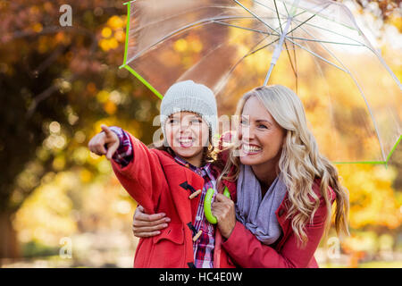 Cheerful girl with mother at park - Stock Photo