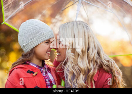 Mother and daughter rubbing noses at park - Stock Photo