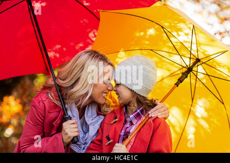 Cheerful mother and daughter with umbrella at park - Stock Photo