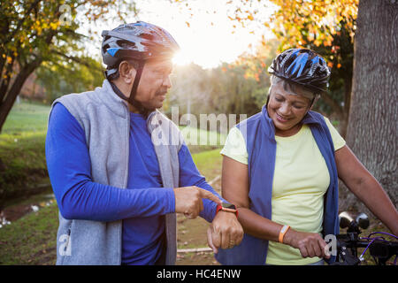 Man pointing his smart watch front of his wife - Stock Photo