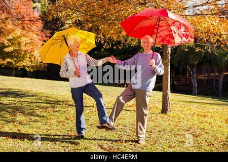 Senior couple dancing with umbrellas - Stock Photo