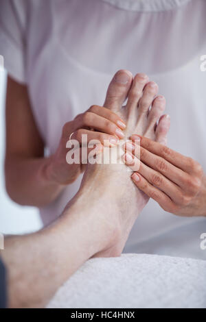 Physiotherapist giving foot massage to a patient - Stock Photo