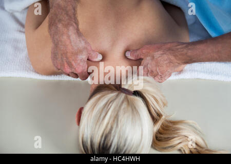 Woman receiving shoulder massage from physiotherapist - Stock Photo