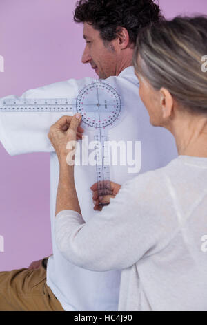 Physiotherapist measuring male patients back with medical ruler - Stock Photo