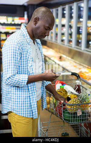 Man using mobile phone in grocery section while shopping - Stock Photo