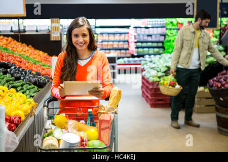 Woman using digital tablet while shopping in supermarket - Stock Photo