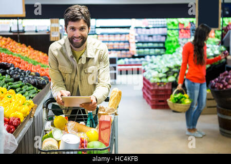 Man using digital tablet while shopping in supermarket - Stock Photo