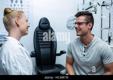 Female optometrist interacting with patient - Stock Photo