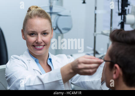 Female optometrist prescribing spectacles to patient - Stock Photo