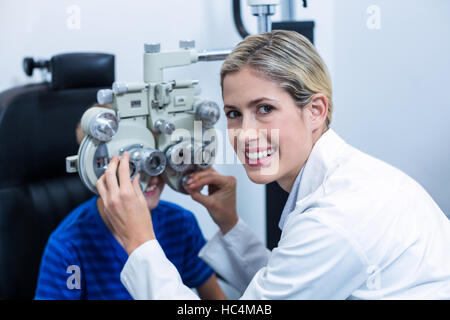 Female optometrist examining young patient on phoropter - Stock Photo