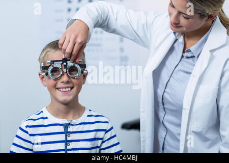 Female optometrist examining young patient with phoropter - Stock Photo