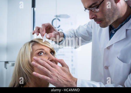 Optometrist putting drops into patients eyes - Stock Photo