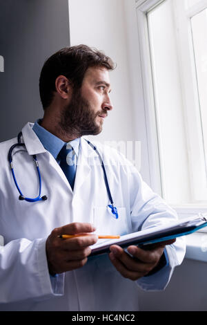 Doctor looking through window while holding clipboard - Stock Photo