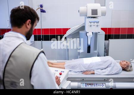 Doctor using x-ray machine to examine patient - Stock Photo