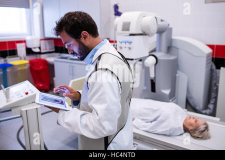 Doctor using digital tablet and patient lying on x ray machine - Stock Photo
