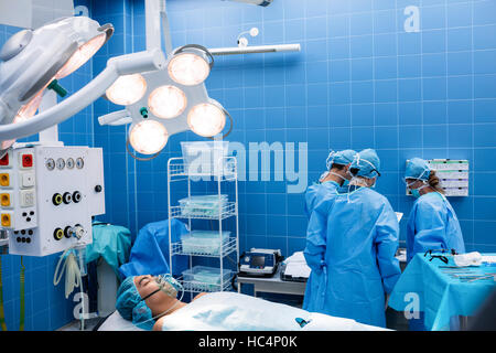 Surgeons interacting with each other while patient lying on operation bed - Stock Photo