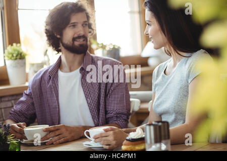 Couple interacting with each other while having coffee - Stock Photo