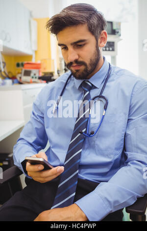 Doctor text messaging on mobile phone - Stock Photo