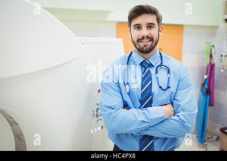 Portrait of doctor standing near mri scanner - Stock Photo