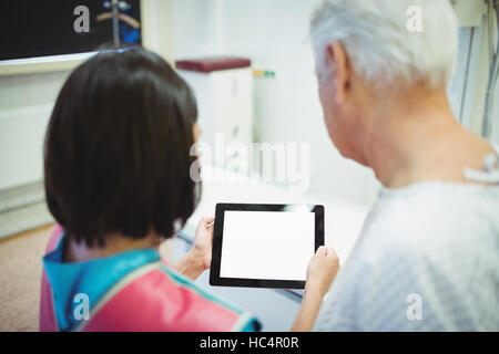 Female doctor discussing with patient over digital tablet - Stock Photo