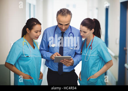 Doctor and nurses discussing over digital tablet - Stock Photo