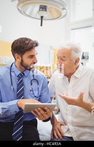 Doctor discussing with patient over digital tablet - Stock Photo