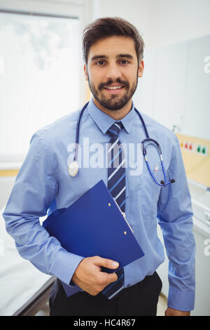 Portrait of smiling doctor holding clipboard - Stock Photo