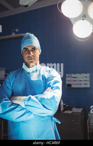Portrait of surgeon standing with arms crossed in operation room - Stock Photo