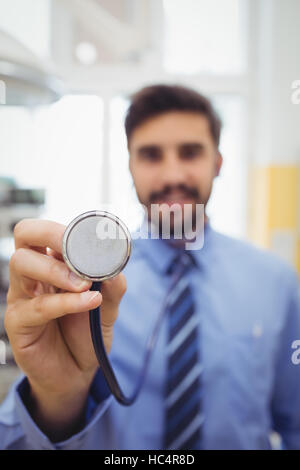 Portrait of smiling doctor holding stethoscope - Stock Photo