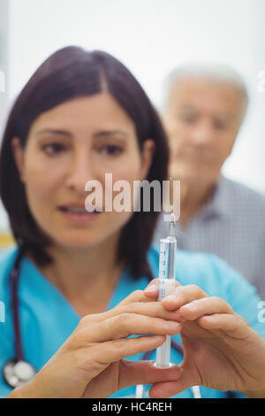 Female doctor holding an injection - Stock Photo