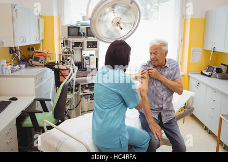 Female doctor giving an injection to a patient - Stock Photo