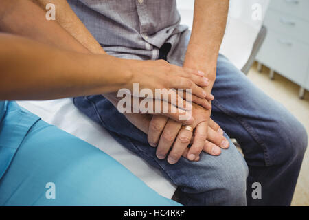 Close-up of female doctor consoling a patient - Stock Photo