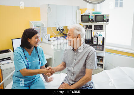 Female doctor shaking hands with patient - Stock Photo