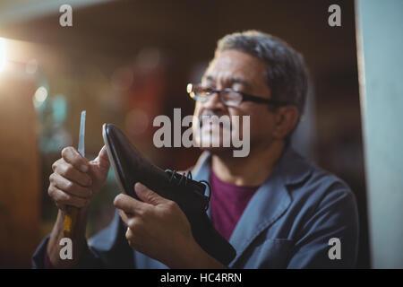 Shoemaker repairing a shoe - Stock Photo