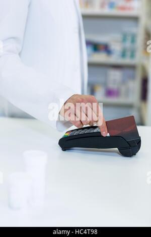 Pharmacist swiping card through payment terminal - Stock Photo