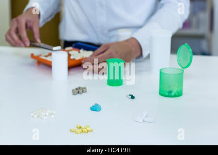 Pharmacist putting pill in container at pharmacy - Stock Photo