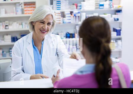 Pharmacist giving prescriptions of medicine to customer - Stock Photo