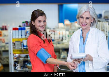Pharmacist checking blood pressure of customer in pharmacy - Stock Photo