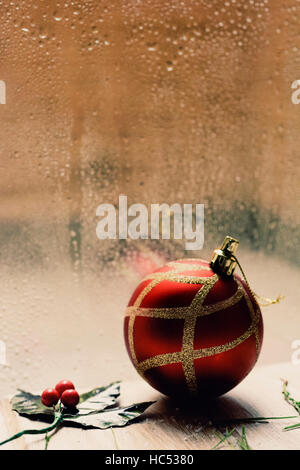 a twig of holly and a red and golden christmas ball on a rustic wooden table in front of a window splattered with - Stock Photo