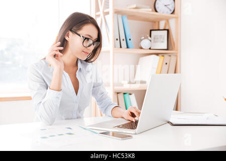 Photo of businesswoman dressed in white shirt and wearing glasses sitting in her office and using laptop. - Stock Photo