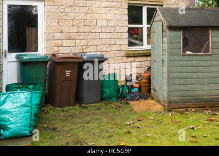 Garden shed, refuse bins, recycling bins and garden waste bags lined up by the garage in a private garden - West - Stock Photo