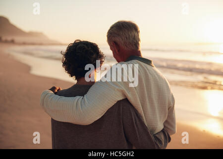Rear view shot of a senior couple walking on the sea shore. Loving mature couple spending leisurely time on the - Stock Photo