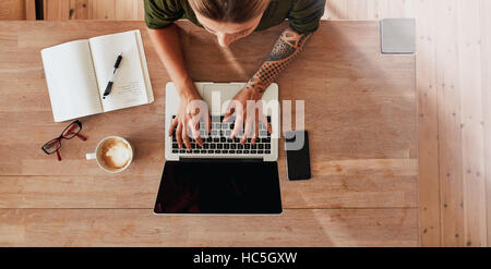 Top view of woman hands typing on laptop. Female sitting at cafe table with laptop, mobile phone, diary, coffee - Stock Photo