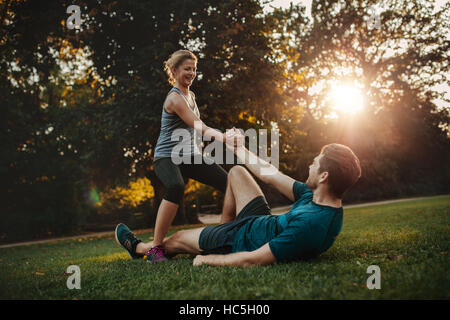 Shot of young woman helping man to get up from ground. Healthy young couple at park exercising together. - Stock Photo
