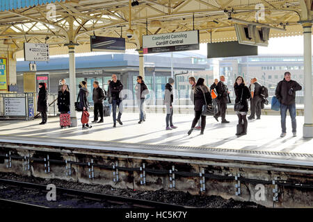 People waiting for a train standing on the platform at Cardiff Railway Station in autumn sunshine Cardiff Wales - Stock Photo